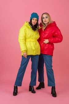 Two attractive girls posing on pink background in colorful winter down jacket of bright red and yellow color