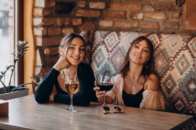 Две привлекательные девушки сидят в кафе и пьют вино