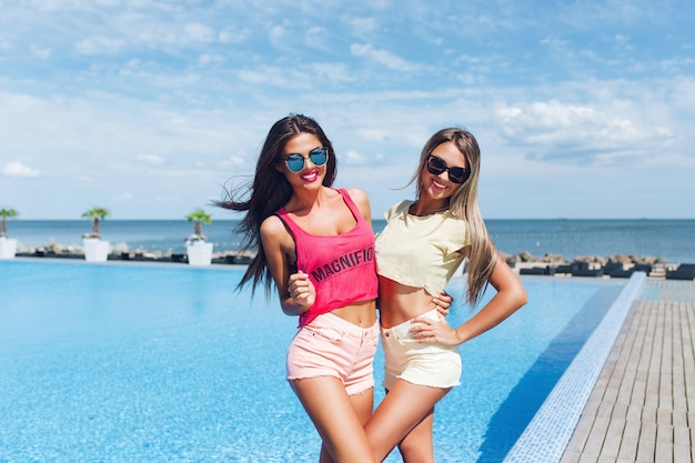 長い髪の2人の魅力的な女の子が太陽の下でプールの近くでポーズをとっています。彼らはカメラに微笑んでいます。