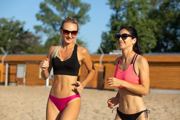Two attractive middle-aged female joggers wearing sunglasses and swimsuit training at the beach