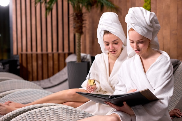 Two attractive relaxed women looking at menu in spa salon choosing procedures