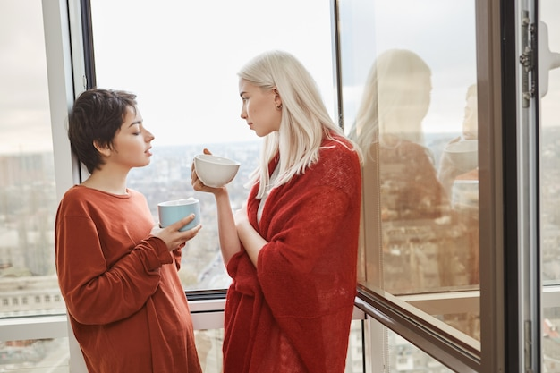 Two attractive and sensual womanfriends standing near opened window in red clothes while drinking coffee