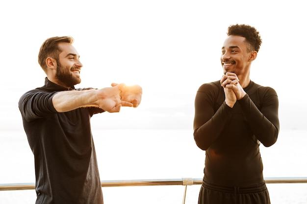 ビーチで屋外で2人の魅力的な笑顔の若い健康なスポーツマン、一緒にトレーニング、ストレッチ運動を行う