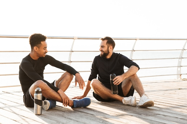 ビーチで屋外に座って、ジョギングの後に休んでいる2人の魅力的な笑顔の若い健康なスポーツマン