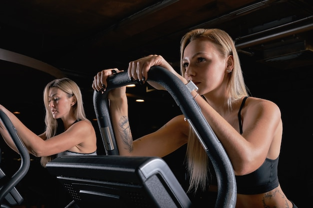 Two attractive sporty women riding exercise bikes during cycling training in gym