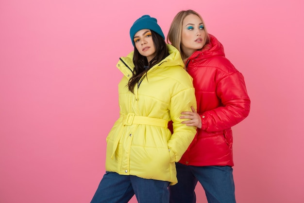 赤と黄色の色のカラフルな冬のダウンジャケット、暖かい服のファッショントレンドでピンクの背景にポーズをとる2人の魅力的なスタイリッシュな女性