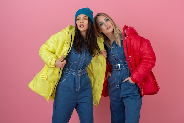 Two attractive stylish women posing on pink wall in colorful winter down jacket of red and yellow color, warm clothes fashion trend