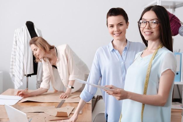 Две привлекательные стильные женщины стоят возле стола в ателье, пока их коллега делает пометки на узорах