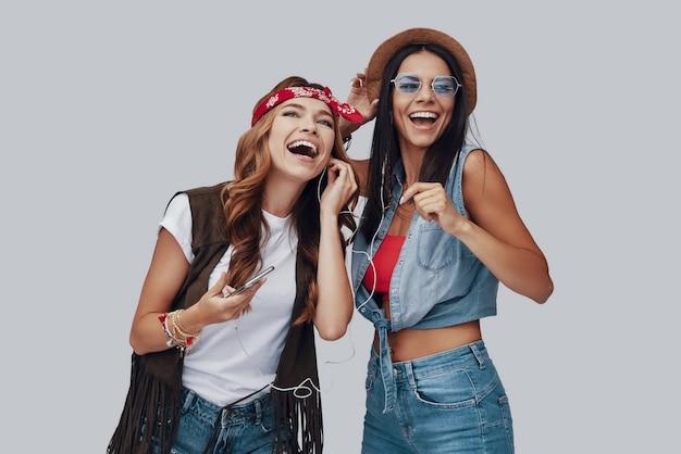 회색 배경에 서있는 동안 웃고 두 매력적인 세련된 젊은 여성
