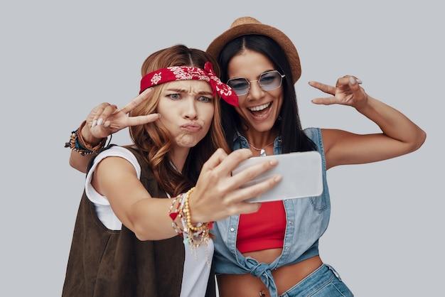 회색 배경에 서있는 동안 셀카를 복용하고 웃는 두 매력적인 세련된 젊은 여성