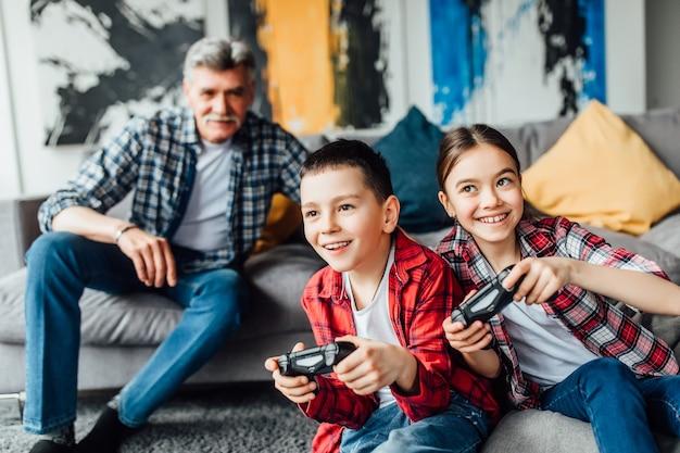 Due adolescenti attraenti e una ragazza stanno giocando alla console di gioco e sorridono mentre sono seduti sul divano di casa.