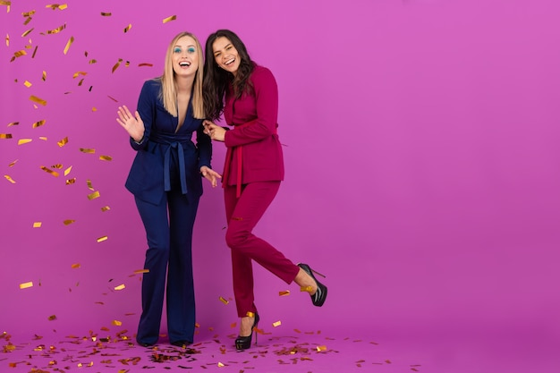 Две привлекательные женщины празднуют новый год на фиолетовой стене в стильных красочных вечерних костюмах фиолетового и синего цвета, друзья веселятся вместе, модная тенденция, настроение вечеринки с золотым конфетти