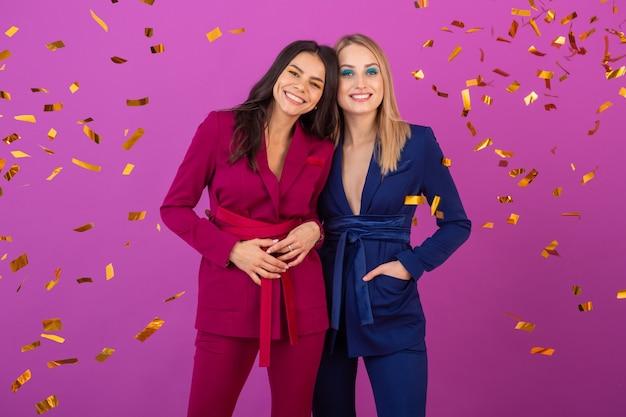 보라색과 파란색의 세련된 화려한 이브닝 정장에 보라색 벽에 새해를 축하하는 두 명의 매력적인 여성, 친구가 함께 재미, 패션 트렌드, 황금색 색종이 파티 분위기