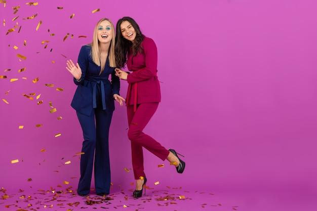 Due donne attraenti che celebrano il nuovo anno sul muro viola in eleganti abiti da sera colorati di colore viola e blu, amici che si divertono insieme, tendenza della moda, atmosfera da festa di coriandoli dorati