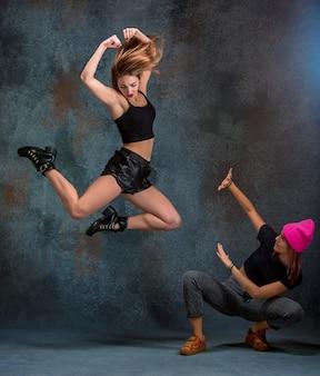 The two attractive women dancing twerk in the studio