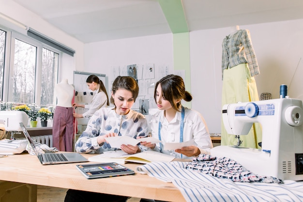 Two attractive women dressmakers designers choosing trendy sketches and materials for new collection of clothes, while young girl designer working on new model tailoring pants on mannequin in studio