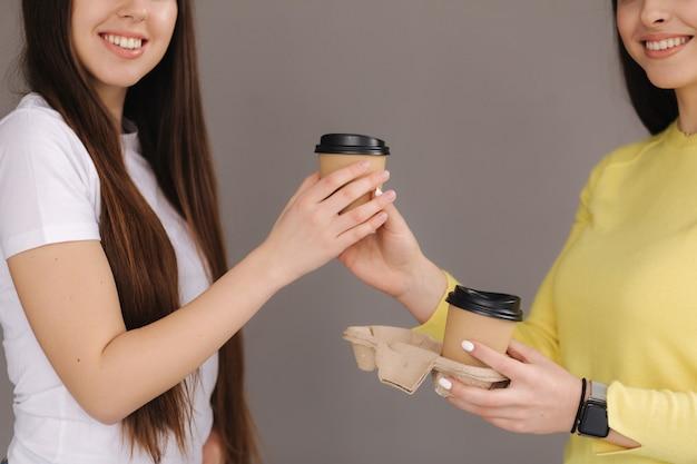 Две привлекательные женщины держат чашку кофе