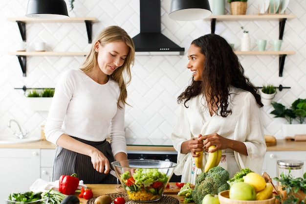 Two attractive women on the kitchen are cooking healthy breakfast from fruits and vegetables