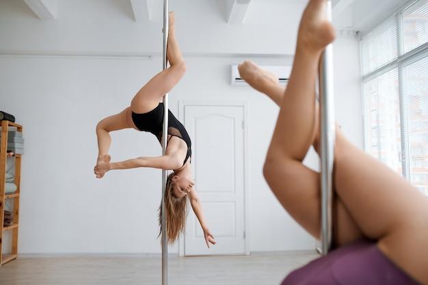 두 명의 매력적인 여성이 수업 시간에 폴 댄스를 연습하고 운동을합니다. 체육관에서 운동하는 전문 여성 댄서, 장대 댄스