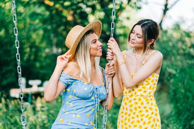 여름 화창한 날 정원에서 그네 근처에 서 있는 두 명의 매력적인 여성.