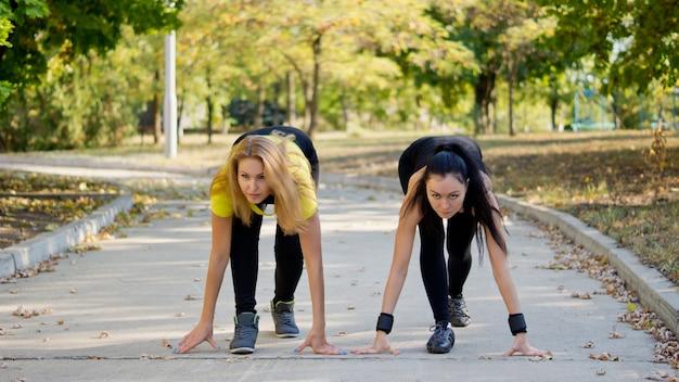 Две привлекательные женщины-товарищи по команде в стартовой позиции во время подготовки к соревнованиям по бегу или спринту