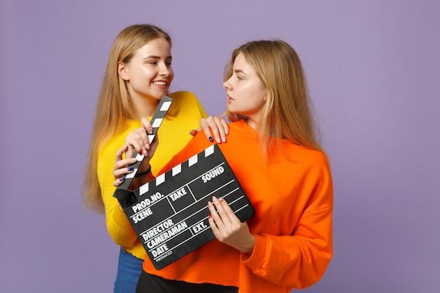 화려한 옷을 입고 두 매력적인 젊은 금발 쌍둥이 자매 여자는 보라색 파란색 벽에 절연 clapperboard 만드는 고전적인 검은 영화를 개최. 사람들이 가족 라이프 스타일 개념. .