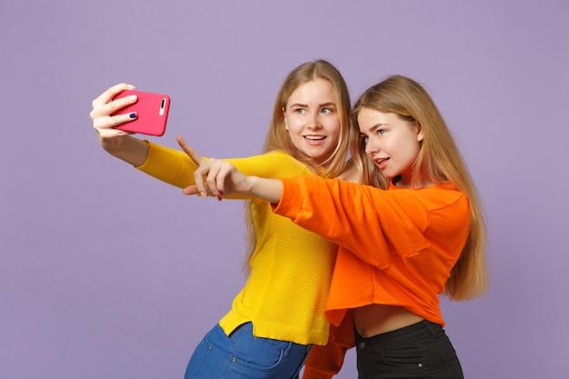 パステルバイオレットブルーの壁に隔離された携帯電話でselfieショットをしている鮮やかな服を着た2人の魅力的な若いブロンドの双子の姉妹の女の子。人々の家族のライフスタイルの概念。