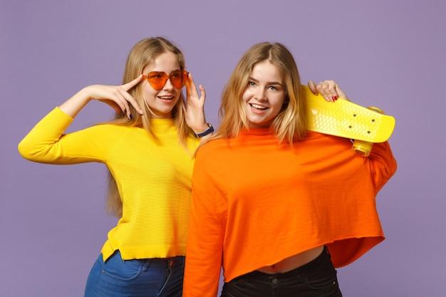 鮮やかな服のハートの眼鏡の2つの魅力的な若いブロンドの双子の姉妹の女の子は、パステルバイオレットブルーの壁に分離された黄色のスケートボードを保持します。人々の家族のライフスタイルの概念。 。