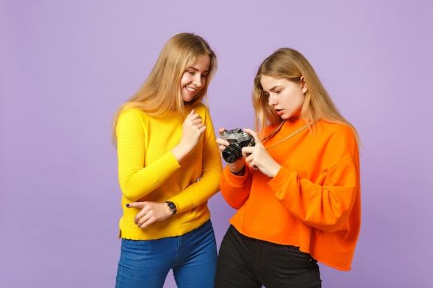 Две привлекательные молодые блондинки сестры-близнецы девушки в яркой красочной одежде держат ретро старинную фотоаппарат, изолированную на фиолетовой синей стене. концепция семейного образа жизни людей.