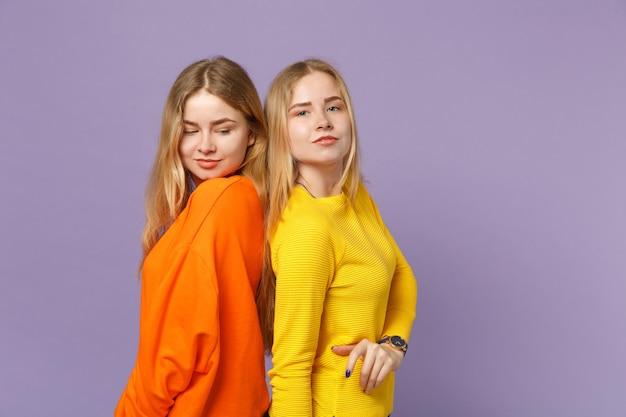 두 매력적인 젊은 금발 쌍둥이 자매 소녀 파스텔 바이올렛 파란색 벽에 연달아 격리 서 생생한 화려한 옷을 입고. 사람들이 가족 라이프 스타일 개념.