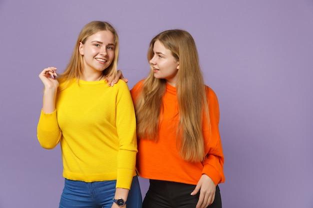 두 매력적인 젊은 금발 쌍둥이 자매 소녀 서, 파스텔 바이올렛 파란색 벽에 고립 된 생생한 화려한 옷을 입고. 사람들이 가족 라이프 스타일 개념.