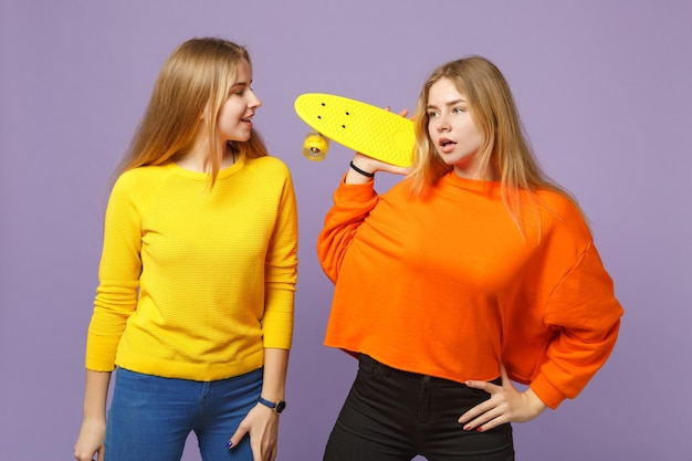 Two attractive young blonde twins sisters girls in vivid colorful clothes holding yellow skateboard isolated on pastel violet blue wall. people family lifestyle concept.