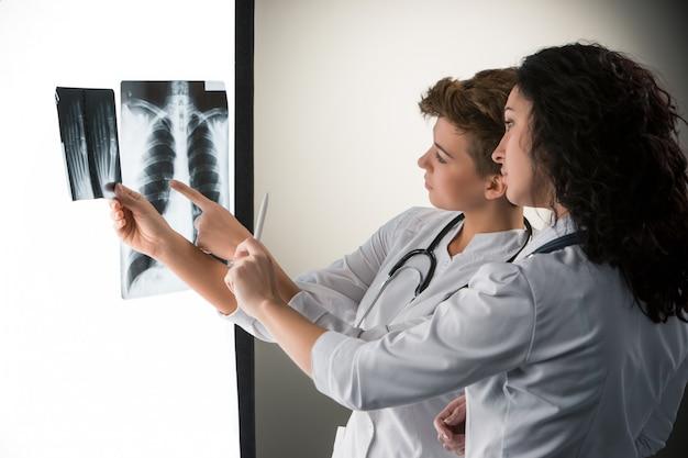 Два привлекательных молодых доктора, смотрящие на результаты рентгена