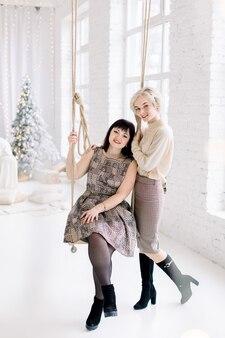 Две привлекательные молодые европейские сестры или подруги, блондинка и брюнетка, в студии