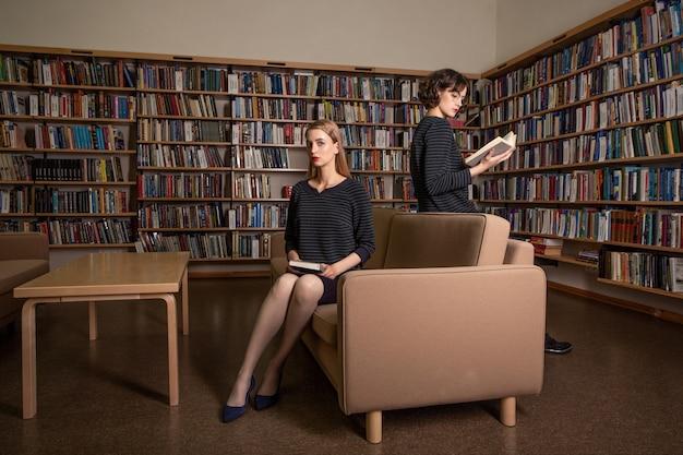 図書館で本を読んでいる2人の魅力的な若い女子学生。