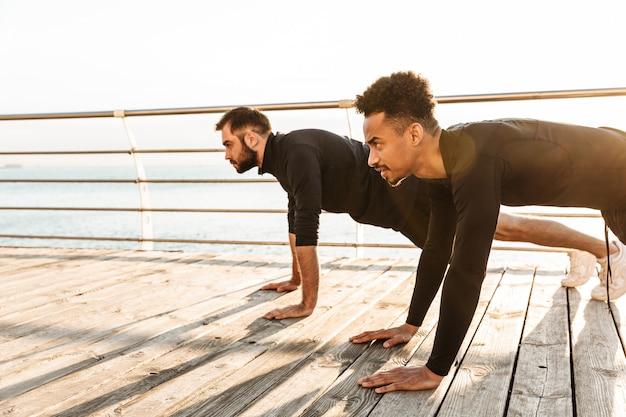 해변에서 야외에서 두 명의 매력적인 젊은 건강한 스포츠맨, 함께 운동하고, 판자 운동
