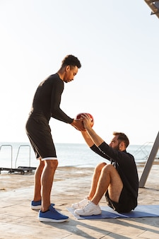 Two attractive young healthy sportsmen outdoors at the beach, workout together, doing exercises with a heavy ball