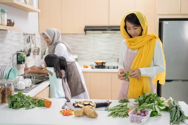 Две привлекательные молодые мусульманские женщины вместе готовят ифтар. рамадан и ид мубарак готовят на кухне