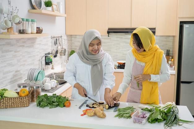 一緒にイフタールディナーを準備している2人の魅力的な若いイスラム教徒の女性。キッチンでラマダンとイードムバラク料理
