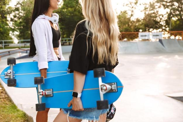 スケートパークに立っている間ロングボードを保持している2人の魅力的な若い10代の少女