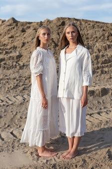 Две привлекательные молодые сестры-близнецы позируют на песчаном карьере в элегантной белой одежде