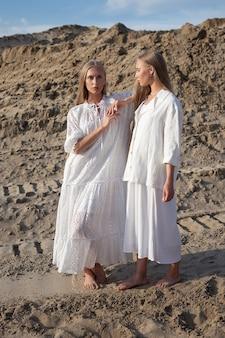 エレガントな白い服を着て砂の採石場でポーズ2つの魅力的な若い双子の姉妹