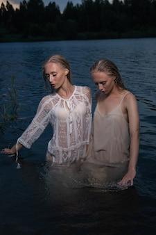 긴 금발 머리가 밤에 호수의 물에 가벼운 드레스를 입고 포즈를 취하는 두 매력적인 젊은 쌍둥이 자매