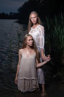 夏の夜に湖の水で軽いドレスでポーズをとって長いブロンドの髪を持つ2つの魅力的な若い双子の姉妹