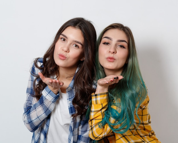 Two attractive young woman with shiny makeup sending air kiss, looking at camera, on white background.