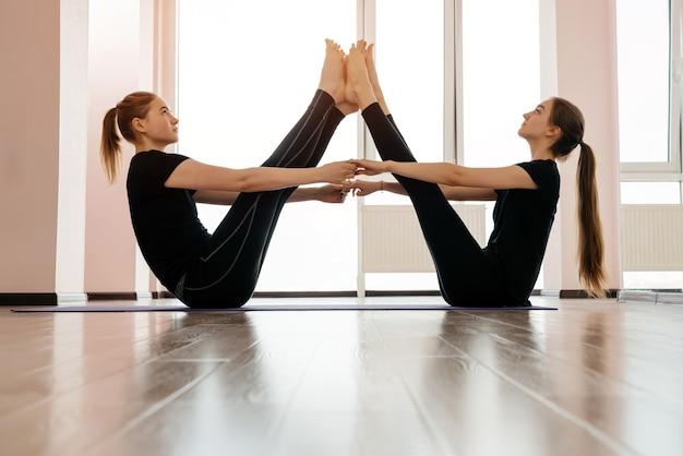 軽いスタジオでバランスを取り、ヨガを練習している2人の魅力的な若い女性。幸福、ウェルネスの概念。高品質の写真