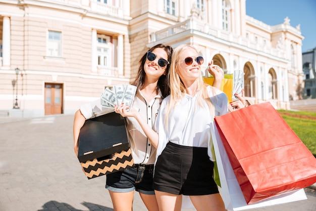 Две привлекательные молодые женщины держат хозяйственные сумки и улыбаются, стоя на открытом воздухе