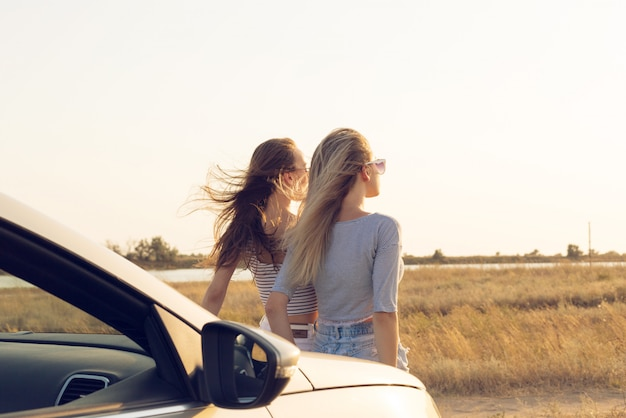 Two attractive young women near a convertible car