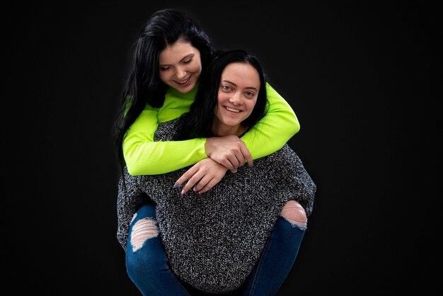 楽しんでいる2人の魅力的な若い女性、1人はもう一方を背負って笑い、暗闇の中で孤立しています