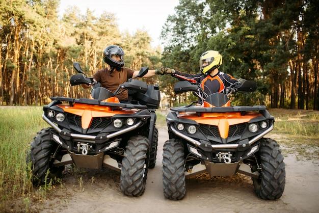 Два гонщика квадроциклов в шлемах бьют кулаками на удачу перед опасной экстремальной ездой по бездорожью, вид спереди, летний лес на заднем плане
